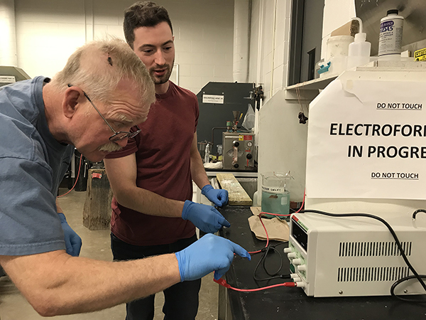 Studio art major Arne Thompson, left, works on electroforming in a lab with Assistant Professor Vincent Pontillo-Verrastro.