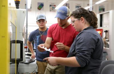 A lab section of Professor Adam Kramschuster's Injection Molding Theory, Design and Application class is photographed in the Plastics Engineering lab in Jarvis Hall Tech Wing.