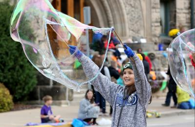 A smiling kid blows a gigantic bubble while watching the annual Homecoming Parade.